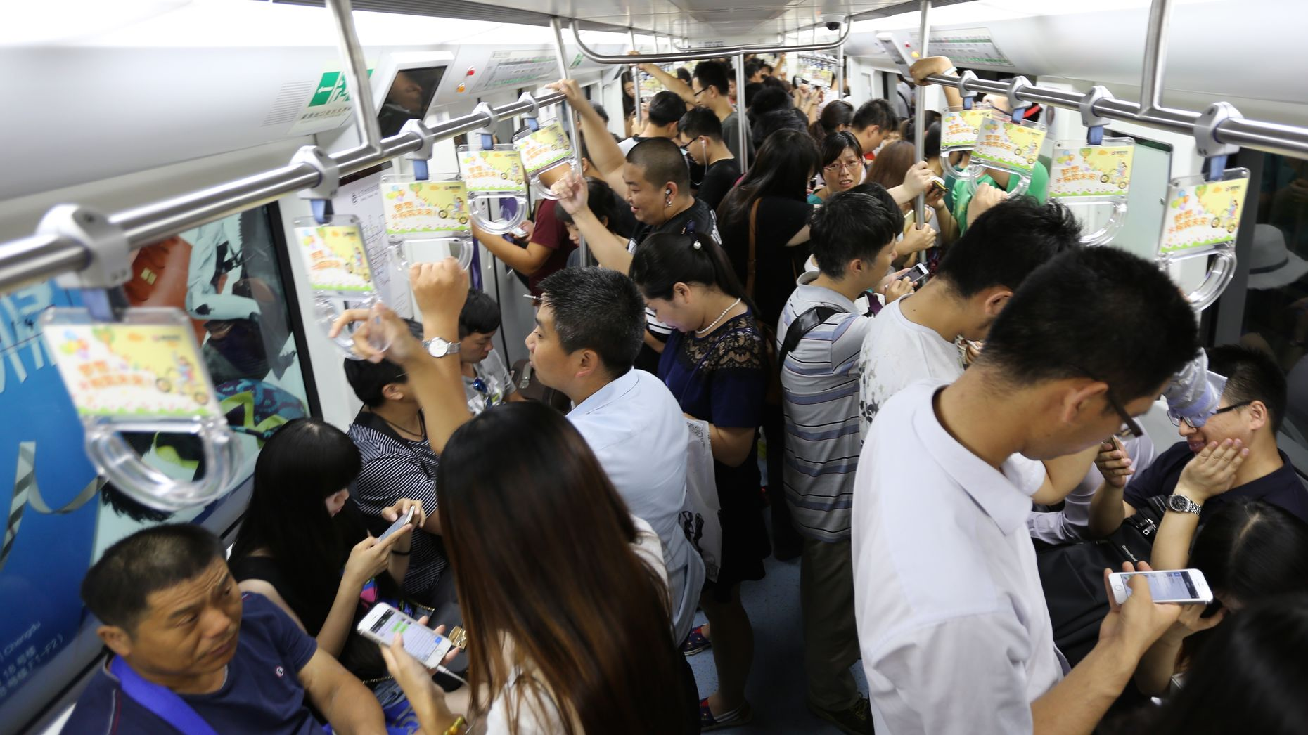 Chinese commuters using WeChat on the Beijing subway. Photo by Hao Xia.