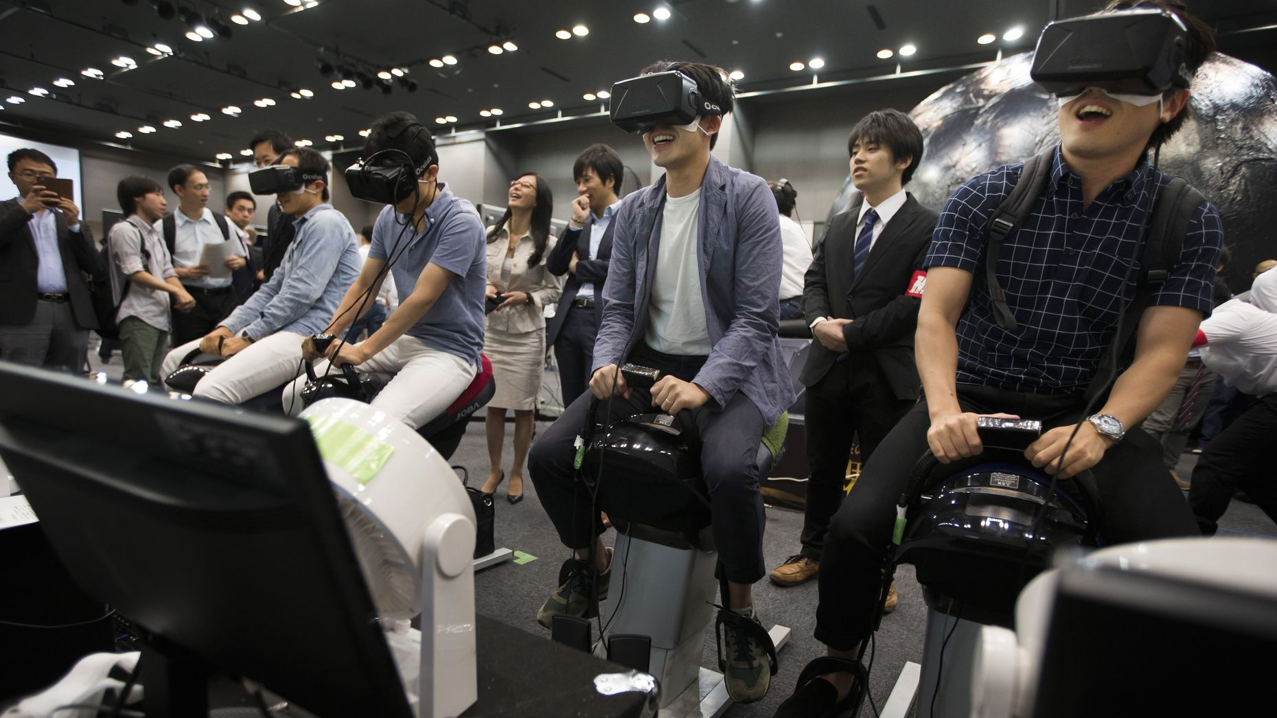 People trying out Oculus Rift headsets at a demonstration in Tokyo last month. Photo by Bloomberg.