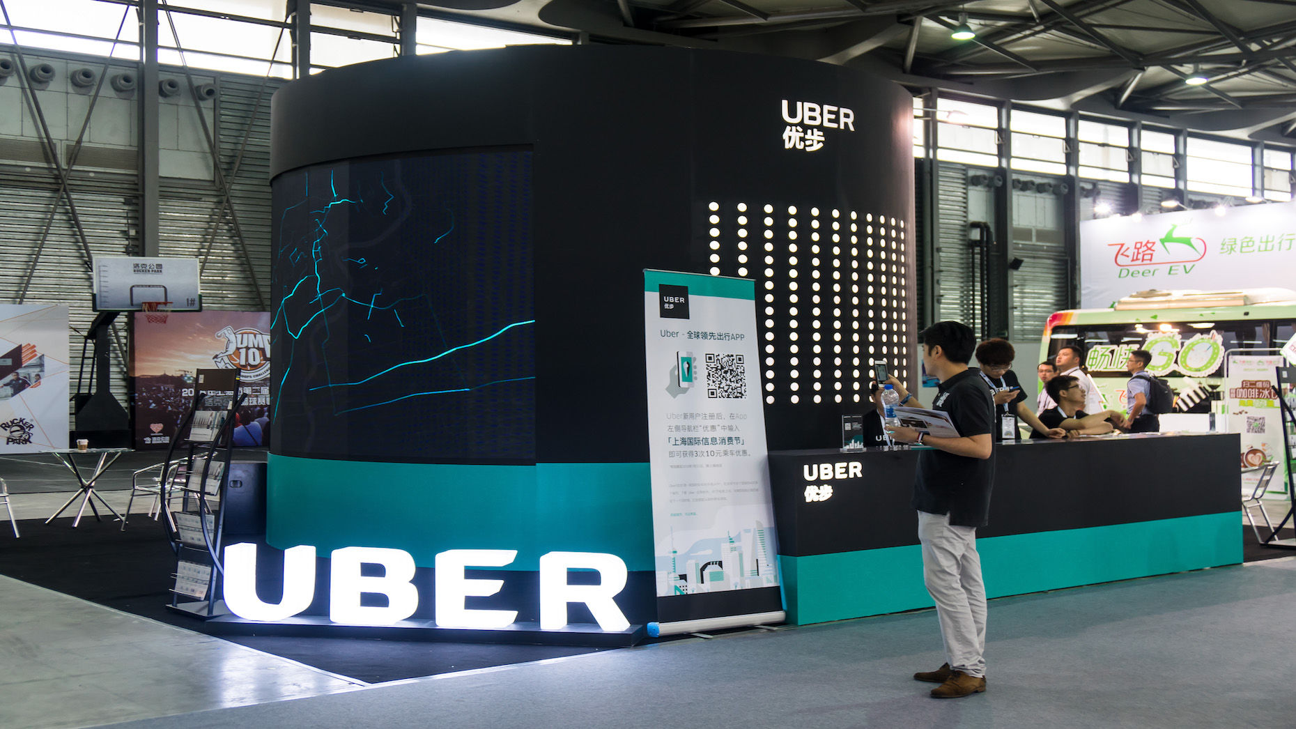 A visitor in front of the Uber stand at the 2016 Mobile World Congress in Shanghai. Photo by The Associated Press.