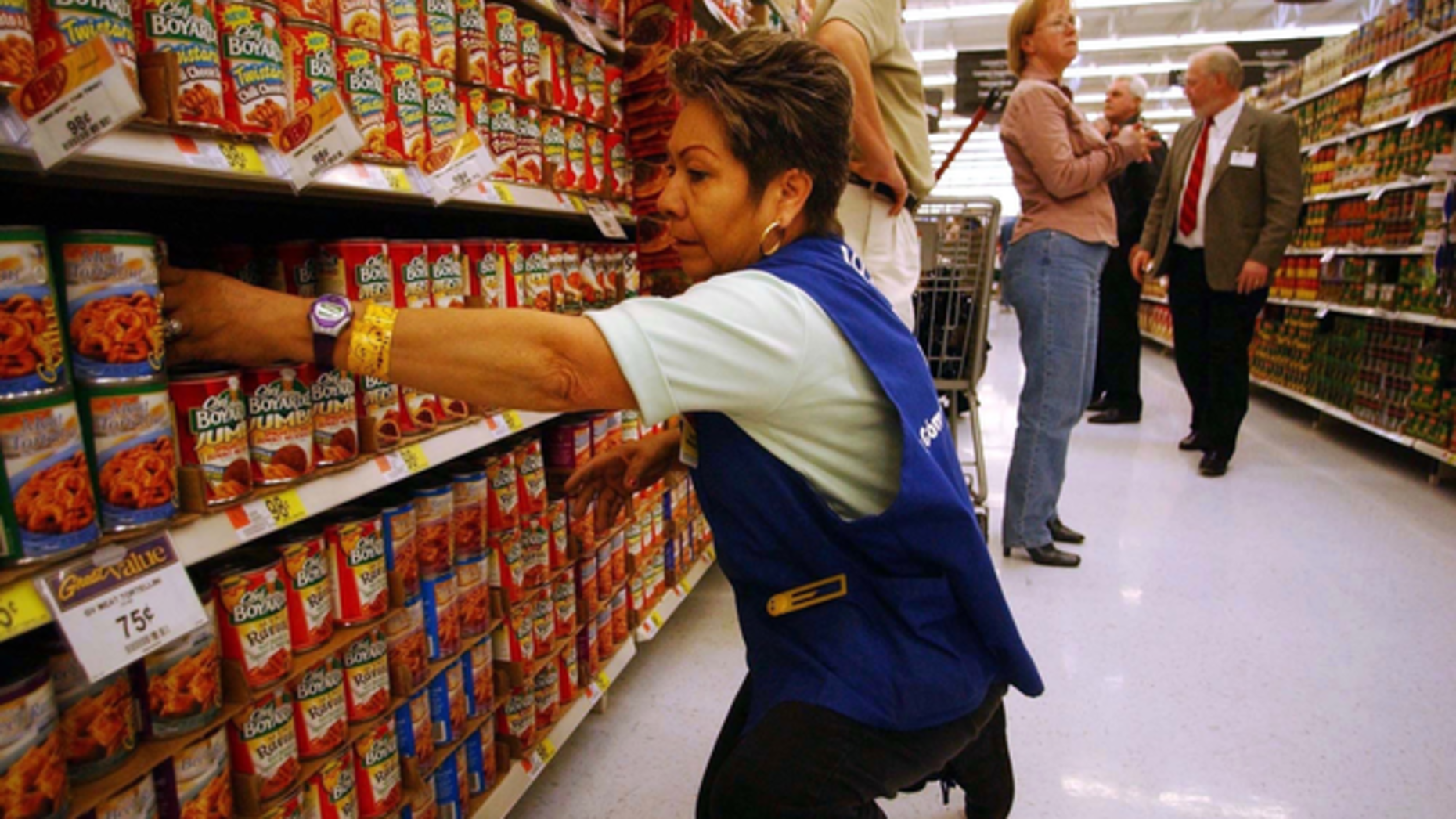 A Walmart employee restocking shelves. Photo by Bloomberg.