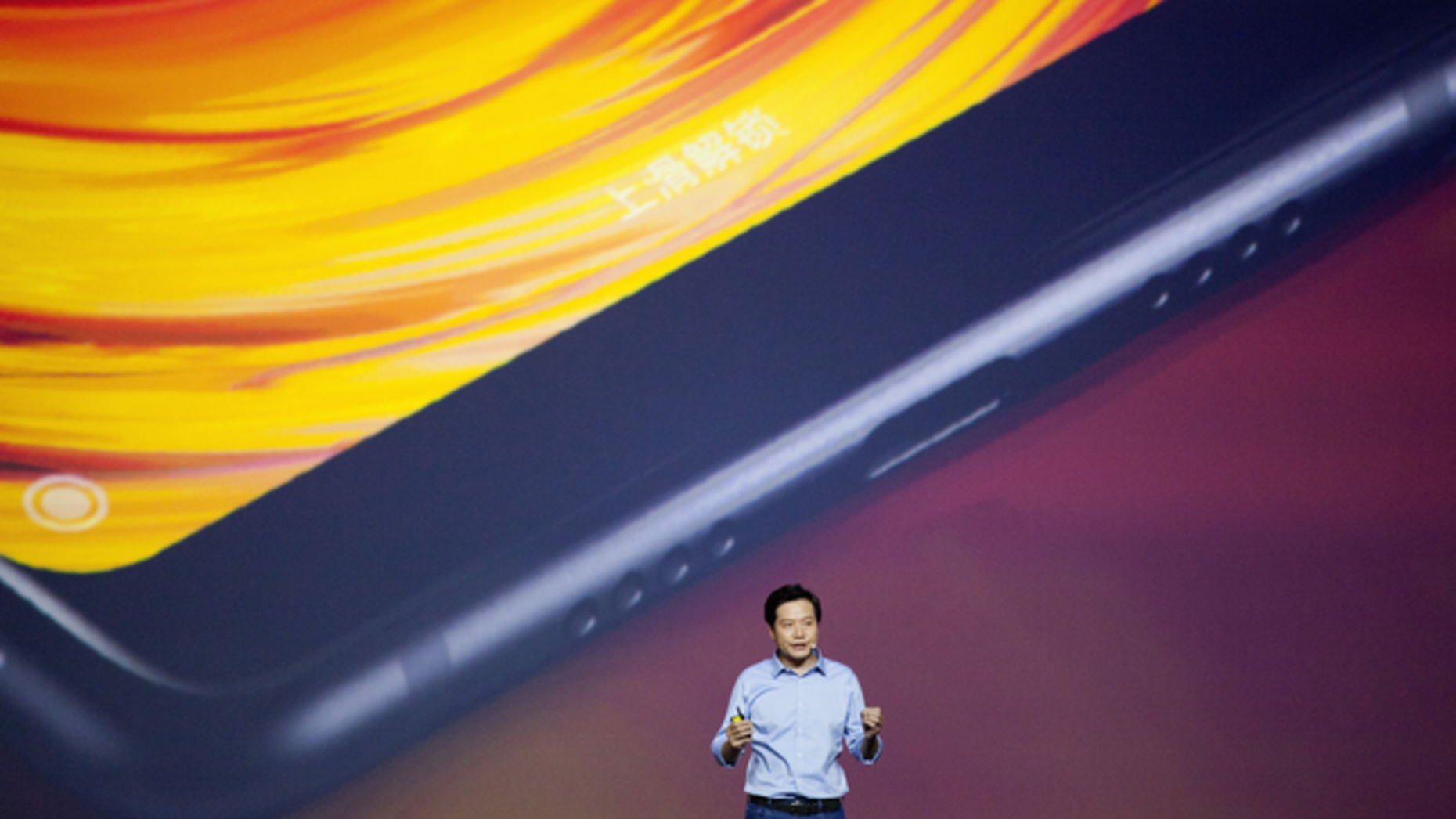 Xiaomi CEO Lei Jun unveiling a new smartphone in China in September. Photo by Bloomberg.