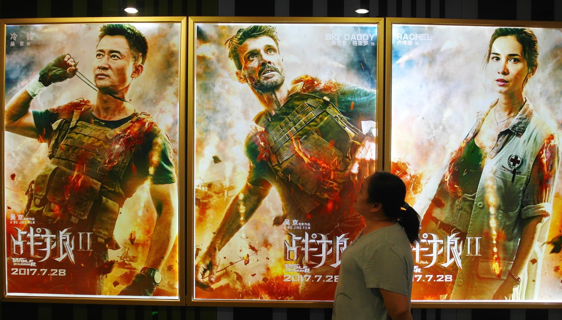 "A Chinese filmgoer walks past posters of  ""Wolf Warriors 2"" at a cinema in Yichang city, central China's Hubei province, last August. Photo by AP."