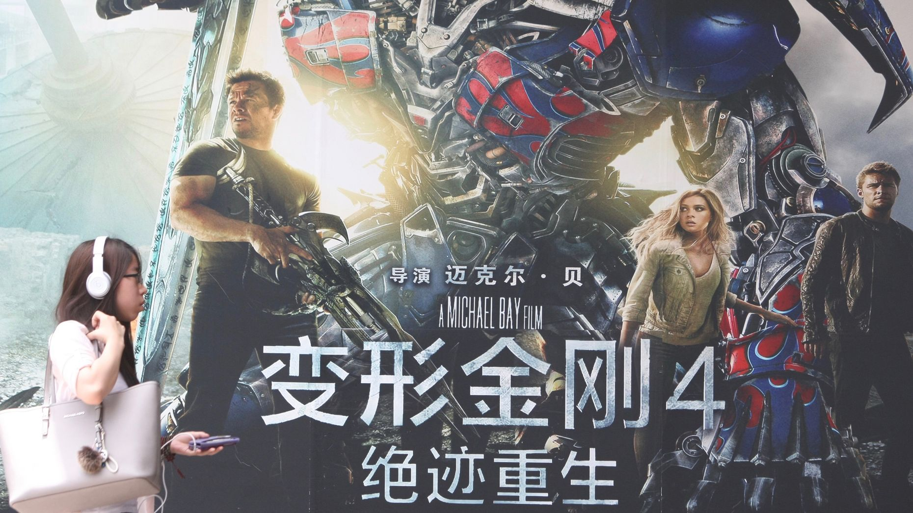 """A pedestrian in Shanghai walks past a poster for """"Transformers: Age of Extinction"""" in 2014. Photo by AP."""