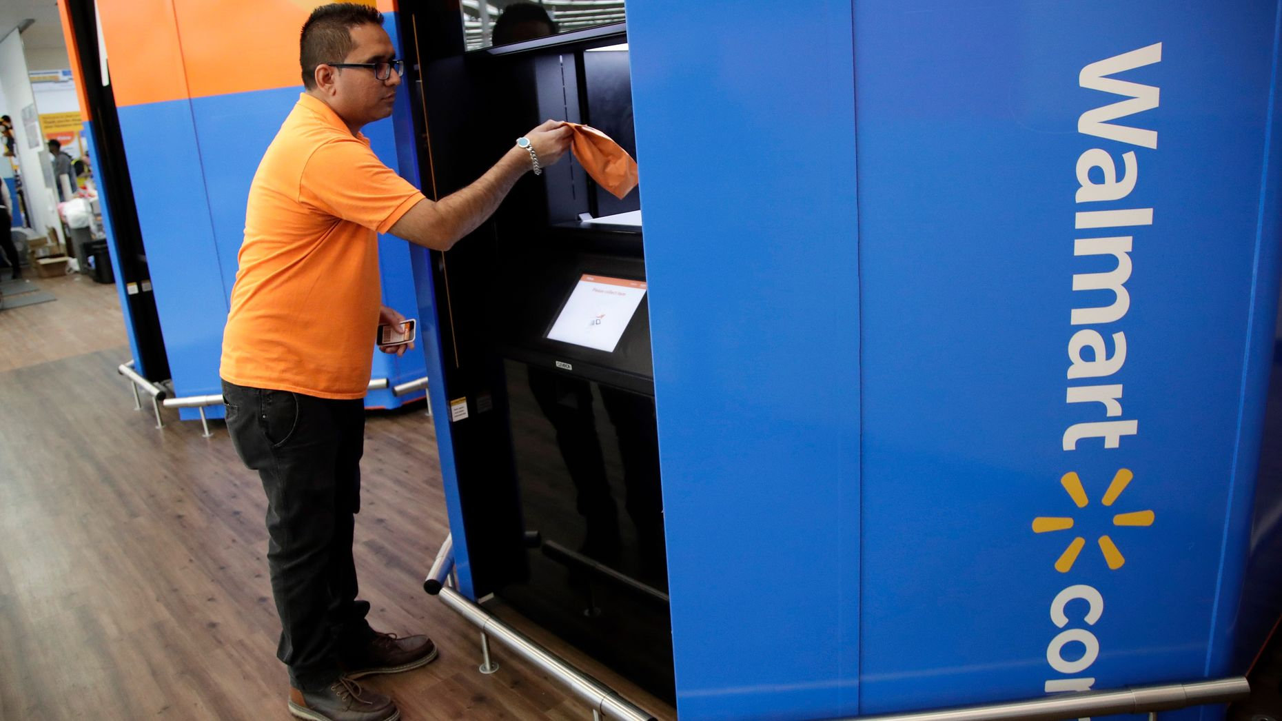 A Walmart manager demonstrating how customers can pick up online orders. Photo by AP