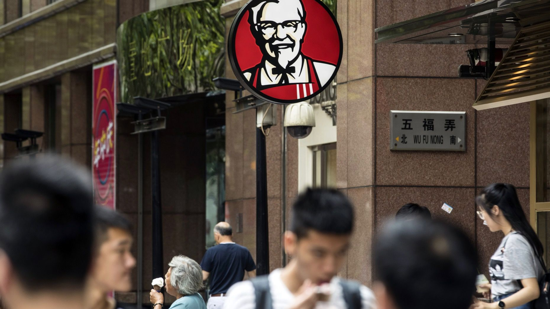 Pedestrians walk past a Yum Brands KFC restaurant in Shanghai. Photo: Bloomberg