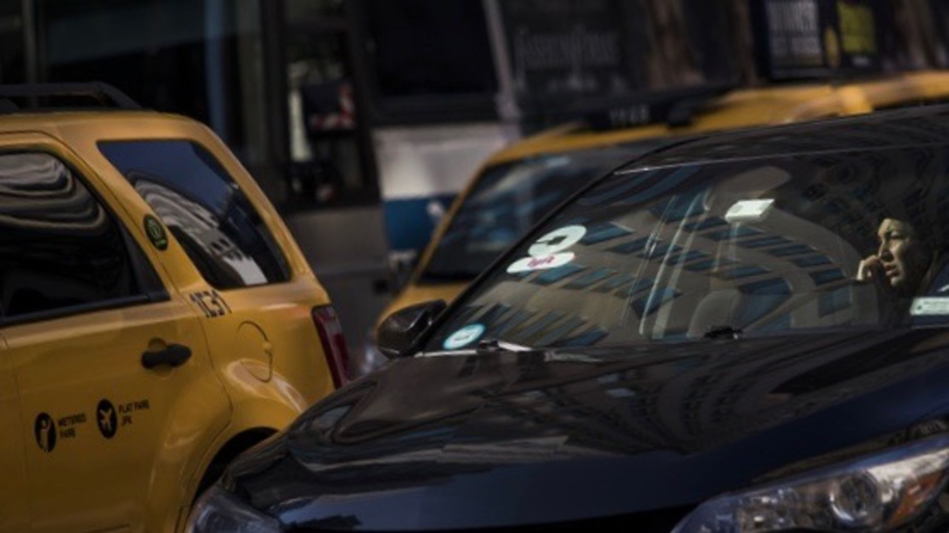 A driver for Uber and Lyft alongside a New York City taxi. Photo by Bloomberg.