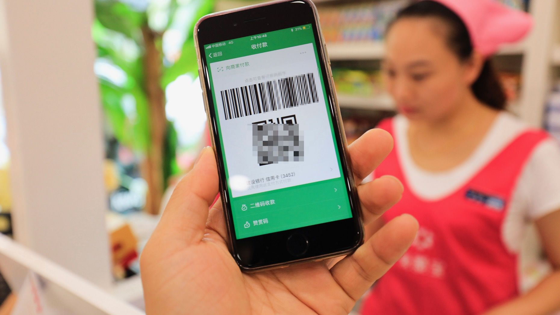 A local resident in Shanghai used a smartphone to have the QR code scanned through Tencent's WeChat Pay. Photo: AP