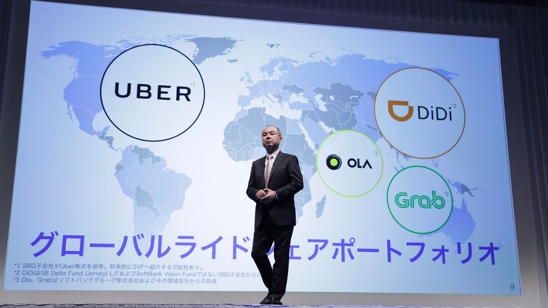 SoftBank CEO Masayoshi Son in front of a map showing ride-hailing firms partly owned by SoftBank. Photo by Bloomberg