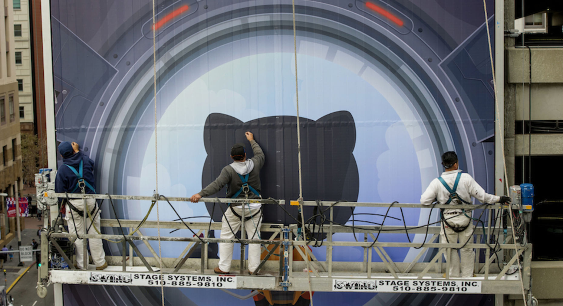 Workers install a billboard for GitHub. Photo by Bloomberg.